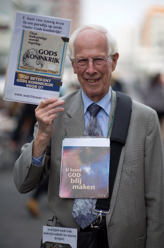 Rotterdam, Netherlands. Elder, Christian man and Jehovah´s Witnesses spreading God´s words in the streets. : Stock Photo