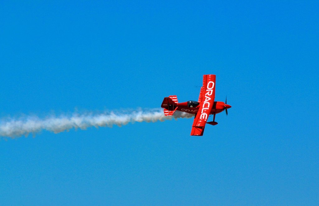 Sean Tucker flies his bright Orange Oracle Challenger through the blue sky over the crowds at Dayton Ohio : Stock Photo