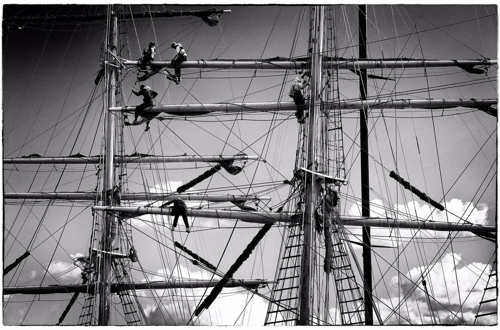 Detalle de marineros trabajando en los mastiles de un barco de epoca, Detail of sailors working on the masts of a vintage yacht, : Stock Photo