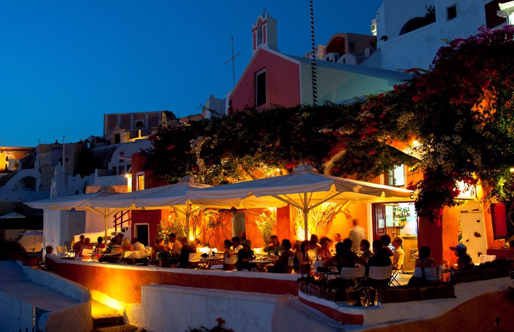 Stock Photo: 1566-1179349 Night exposure after sunset of warm restaurant with tourists on cliff of beautiful Oia in Santorini Greece in Greek Islands