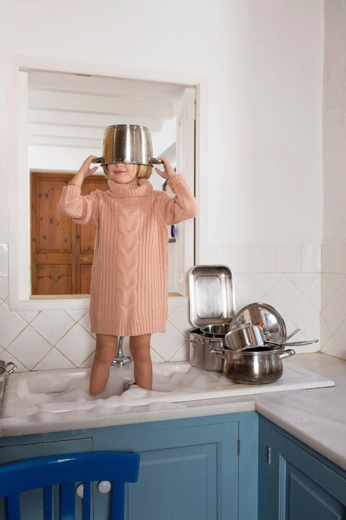 Four year old girl playing in the kitchen sink : Stock Photo
