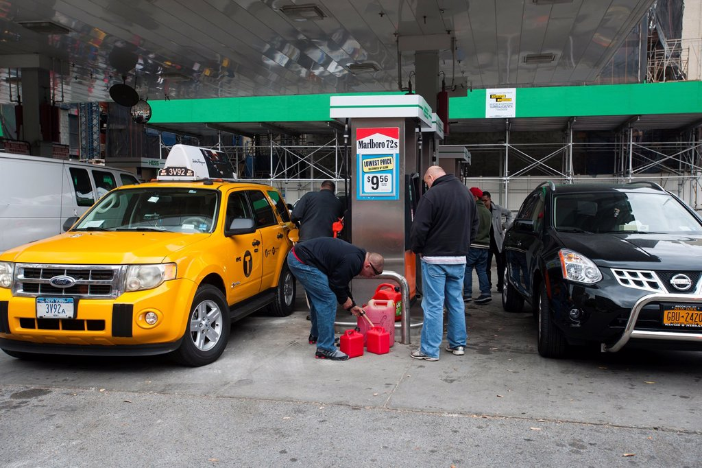 People line up to buy gasoline at a Hess gas station in the Clinton neighborhood of Manhattan in New York Motorists and people with gas cans waited as long as six hours and two hours respectively in order to fill their tanks New York State Governor Andrew. People line up to buy gasoline at a Hess gas station in the Clinton neighborhood of Manhattan in New York Motorists and people with gas cans waited as long as six hours and two hours respectively in order to fill their tanks New York State Gov : Stock Photo