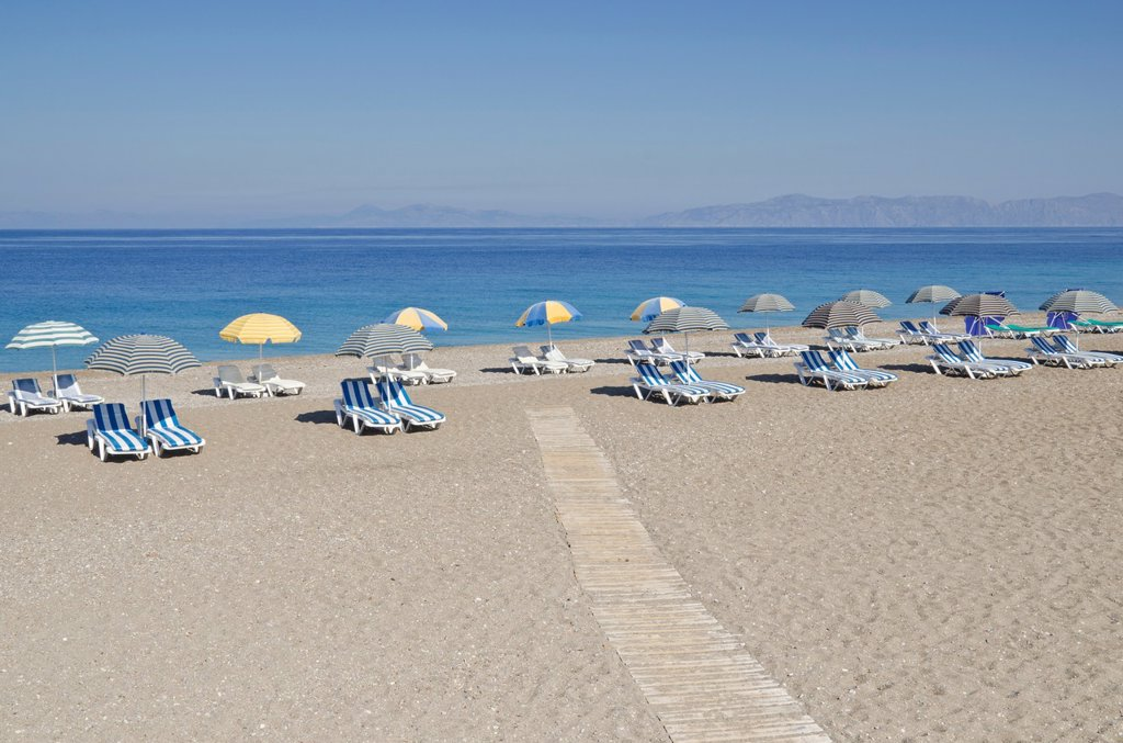 Stock Photo: 1566-1181677 Sunloungers with beach umbrellas on an empty Greek beach on Rhodes Island, Greece