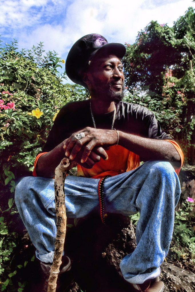 Stock Photo: 1566-1183980 Reggae native man with hat and walking stick in colorful gardens near St John Antigua