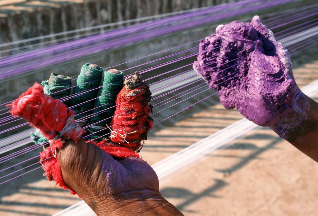 Hands of a man dying strings of kites before the kite flying festival held every spring in Pakistan. Colours are mixed with pieces of glass to strenghten the strings. : Stock Photo