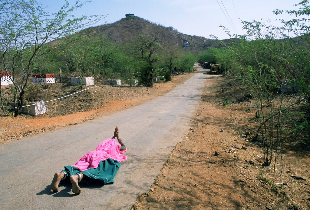 Hindu woman lying on a road while praying. Rajasthan, India. She is going to the temple located on the top of the hill. For kilometers, she walks some steps, then lies on the ground, prays, gets up, walks some steps again, lies on the ground again,... : Stock Photo
