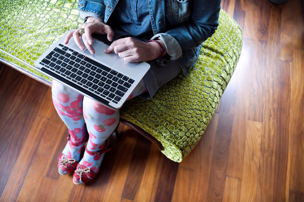 Stock Photo: 1566-1191981 mujer sentada en una chaise longue trabajando con un ordenador portatil, woman sitting on a chaise longue working with a laptop