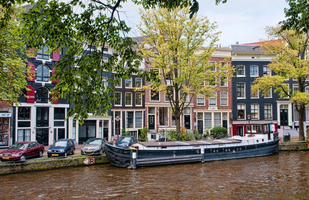 The wonderful canals and buildings beside the river and the tworking local boats on the water in Amsterdam Holland Netherlands in a sunny day : Stock Photo