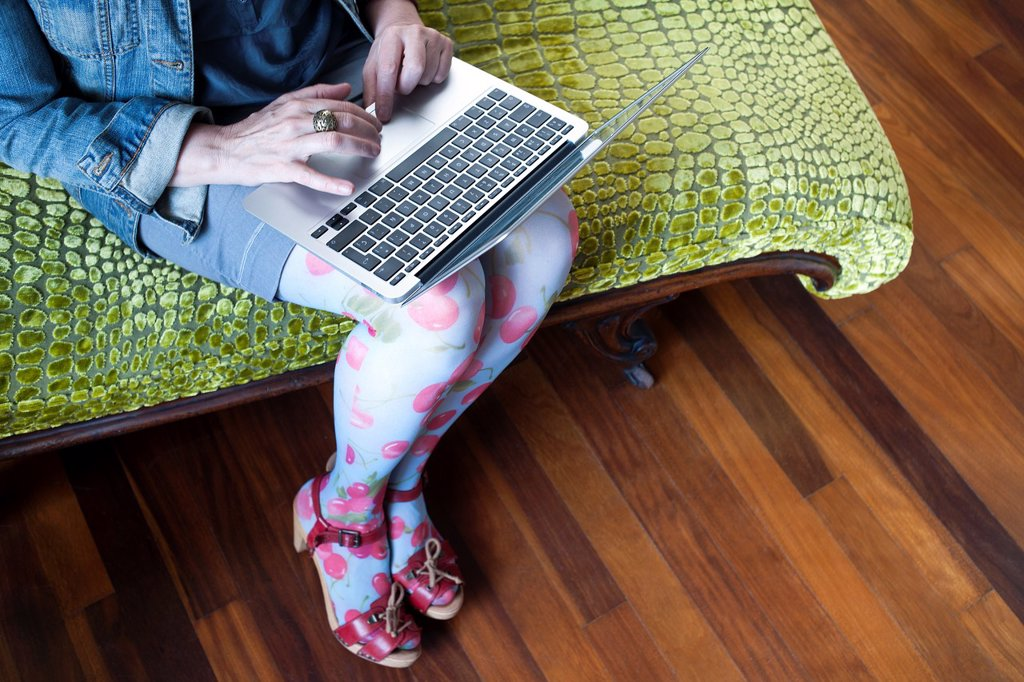 Stock Photo: 1566-1192766 mujer sentada en una chaise longue trabajando con un ordenador portatil, woman sitting on a chaise longue working with a laptop,