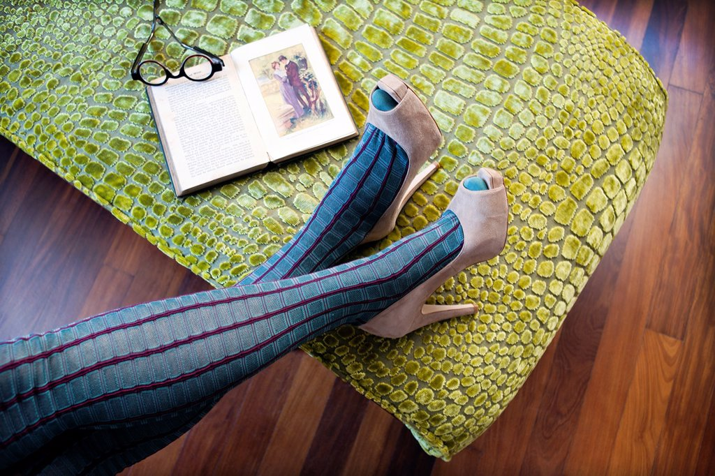 Stock Photo: 1566-1192769 piernas de mujer con zapatos de tacón relajada con un libro, female legs in high heels relaxed with a book