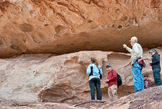 Bob White, voluntary tour guide, visitors at cave with masks, pictographs drawn by Jornada Mogollon peoples, Hueco Tanks State Park and Historic Site, near El Paso, Texas, USA : Stock Photo