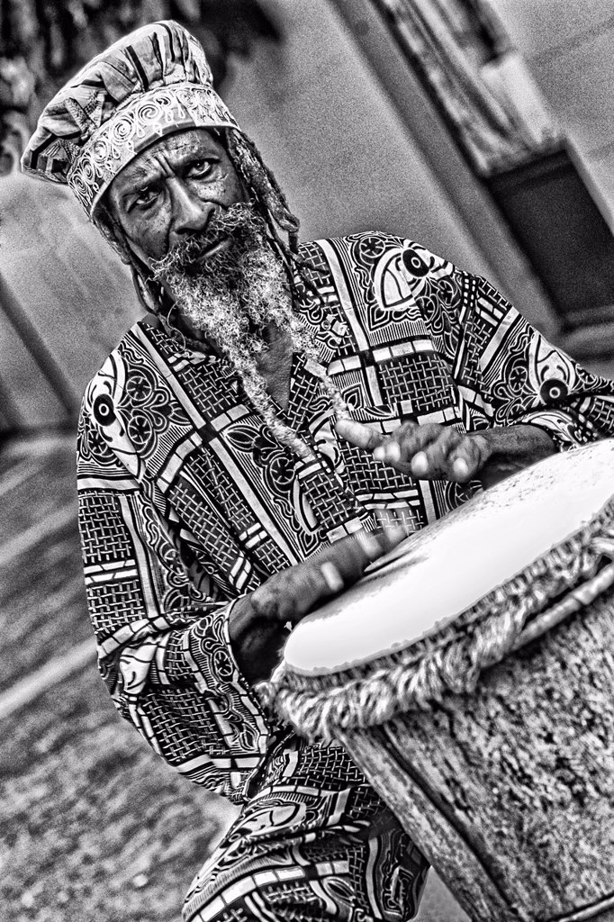 Stock Photo: 1566-1194746 Colorful Rasta Jamaican Reggae performer on drum in costume at Harbour in St John Antigua