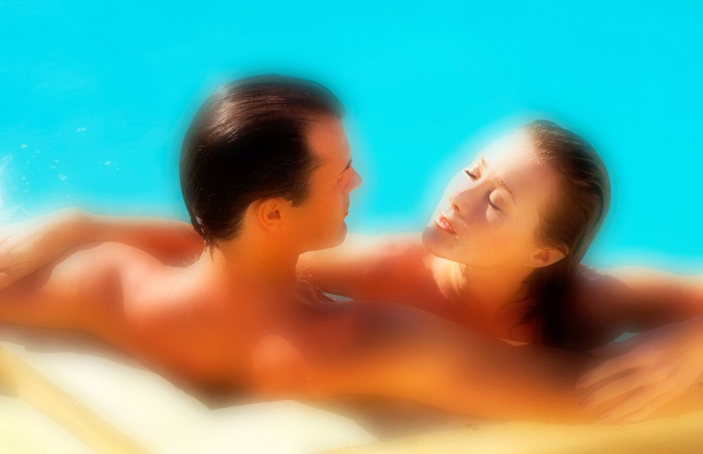 Attractive middle aged couple relaxing in the pool : Stock Photo