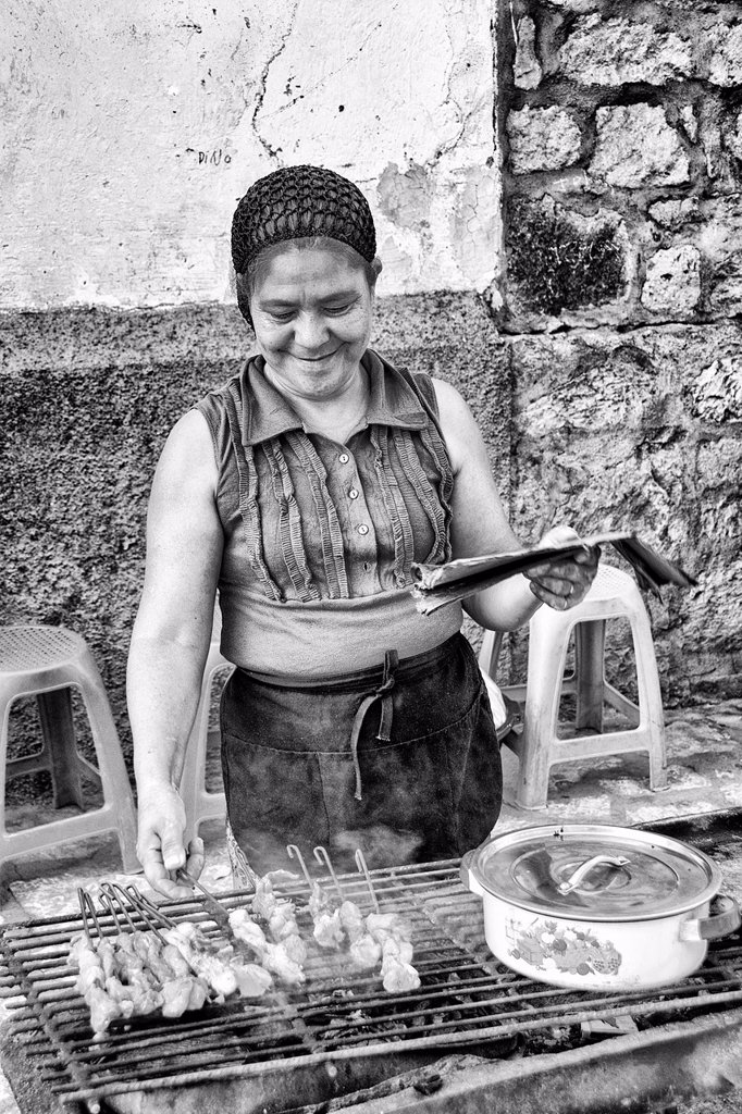 Stock Photo: 1566-1195373 Cooking with local woman on grill for sale in Copan Ruinas Honduras downtown city action