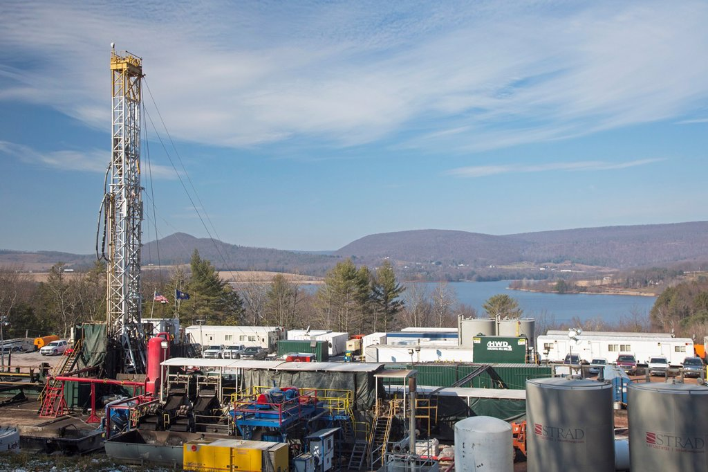 Stock Photo: 1566-1195677 Williamsport, Pennsylvania - An Atlas Energy Resources natural gas well being drilled in rural Lycoming County in preparation for hydraulic fracturing fracking  In the background is Rose Valley Lake