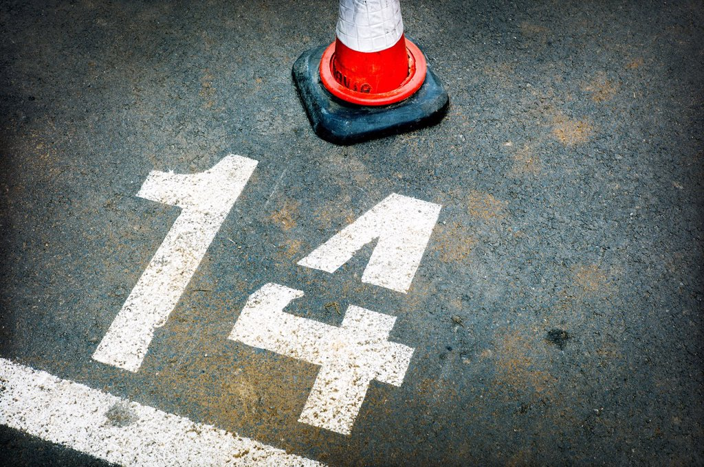 urban simbolism, asphalt road marking in a parking, number fourteenth : Stock Photo