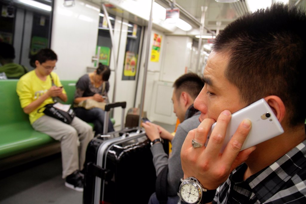 Stock Photo: 1566-1198944 China, Shanghai, Metro, subway, public transportation, riders, Asian, man, woman, Green Line 2, using smartphone,