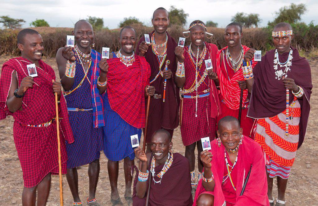 Kenya Africa Amboseli Maasai tribe village Masai group of men in red costume dress and beads holding Fuji Polaroids in remote area of Amboseli National Park safari 1 : Stock Photo