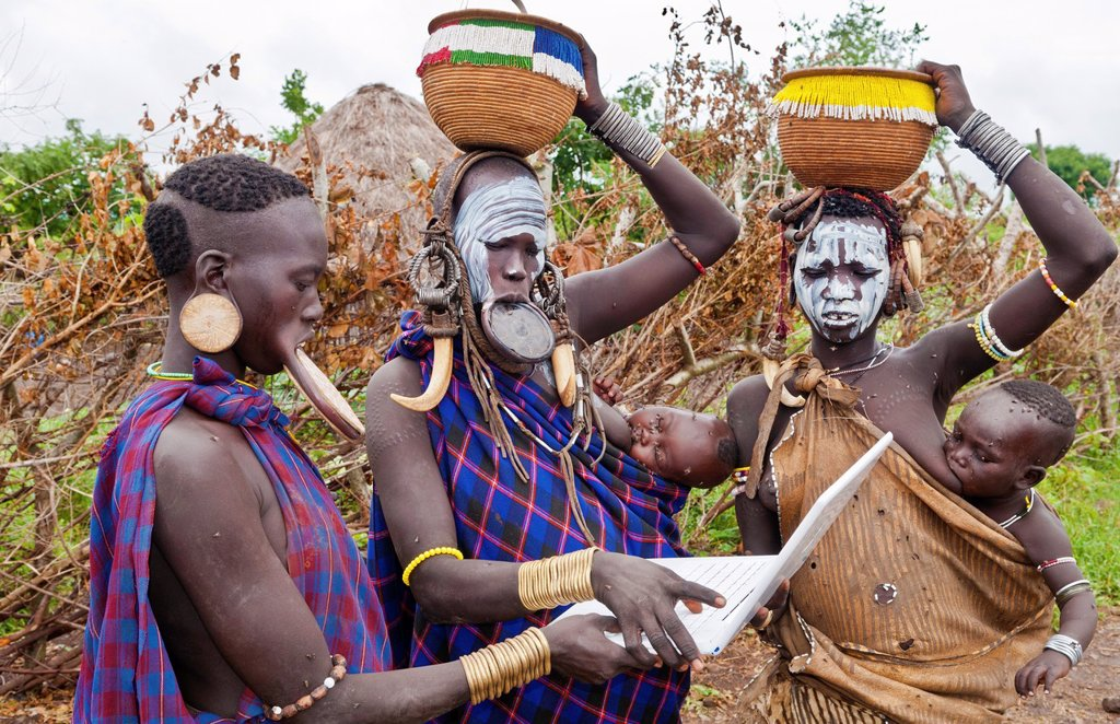 Jinka Ethiopia Africa village Lower Omo Valley Mago National Park wild tribe Mursi women with clay pots in their lips working on modern computer email in tribal portrait with paint on faces and traditional culture 15 : Stock Photo