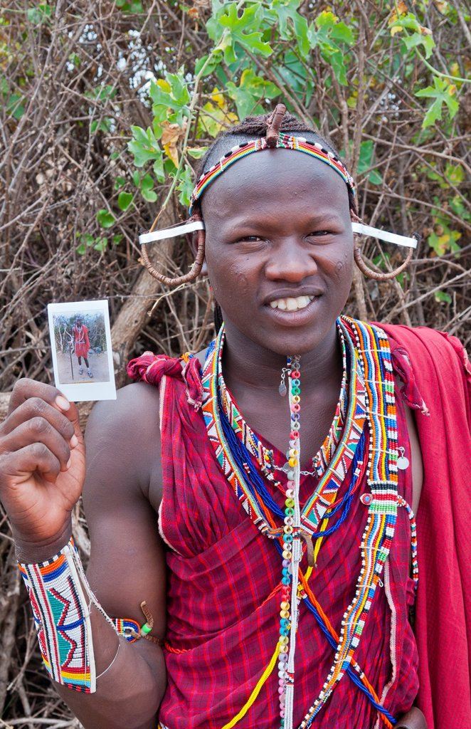 Kenya Africa Amboseli Maasai tribe village Masai man in red costume dress and beads holding Fuji Polaroid in remote area of Amboseli National Park safari 1 : Stock Photo