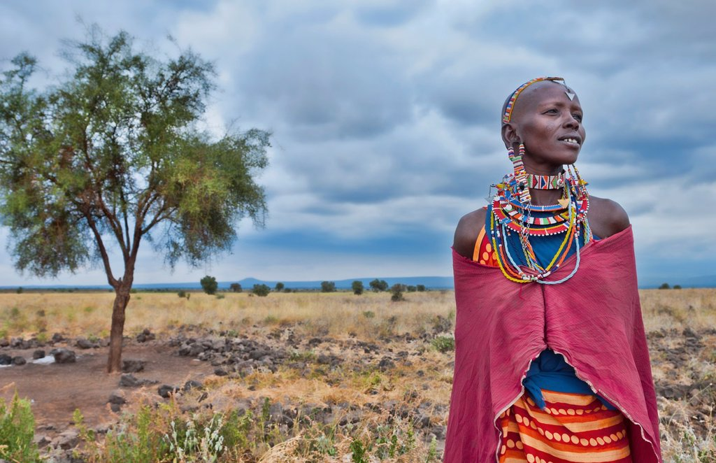 Kenya Africa Amboseli Maasai tribe village Masai woman in red costume dress and beads and tree in remote area of Amboseli National Park safari 1 : Stock Photo