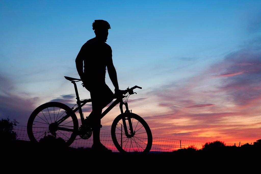 Stock Photo: 1566-1200394 Mountain bike rider resting at dusk