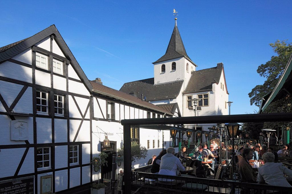 Stock Photo: 1566-1200941 D-Cologne, Rhine, Rhineland, North Rhine-Westphalia, NRW, D-Cologne-Rodenkirchen, church Alt St Maternus, chapel, catholic church, Romanesque style, old ferry house, restaurant, guesthouse Zum Treppchen, people sitting in a sidewalk restaurant
