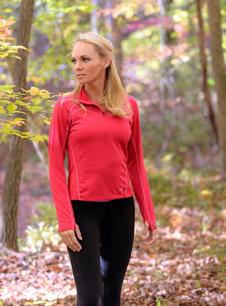 A 38 year old blond woman wearing work-out clothing walking through a forest setting in the fall : Stock Photo