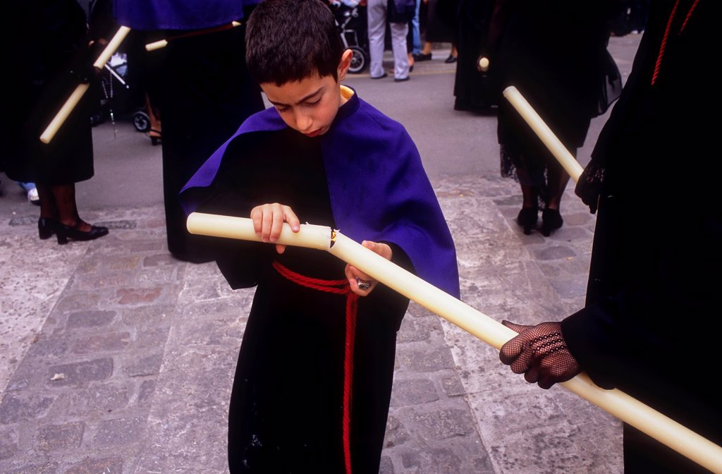 Stock Photo: 1566-1202651 young penitent lighting the candle  Good Friday procession in Calle Carniceria  Brotherhood of `Soledad Campo Principe´  Granada  Andalusia, Spain