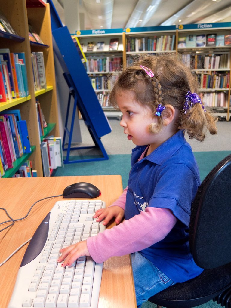 Three year old caucasian girl in preschool top using a computer in a public library. : Stock Photo