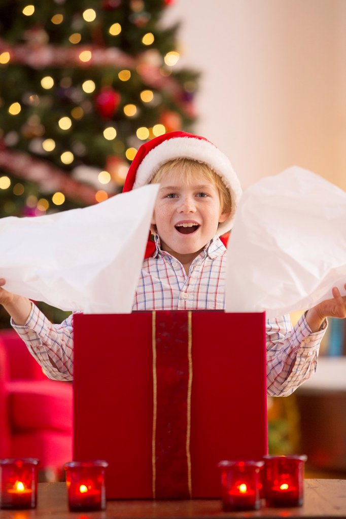 Young boy opening a Christmas present on Christmas day : Stock Photo