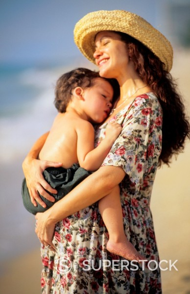 Beautiful pregnant hispanic mother with her young son with love together at beach with waves : Stock Photo