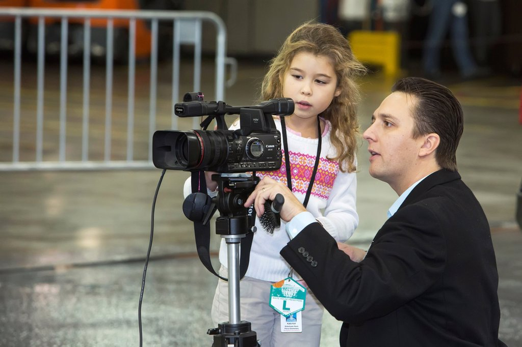 Redford, Michigan - A seven-year-old girl with an adult advisor reports for Kid Witness News during a visit by President Barack Obama to a Detroit Diesel factory  Kid Witness News is a video education program for school children supported by Panasonic : Stock Photo