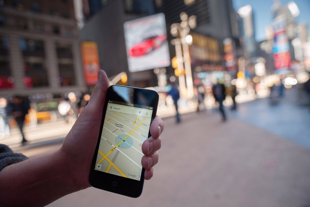 Stock Photo: 1566-1210262 An iPod Touch user displays the Google Maps app on her device in Times Square in New York Google released a version of their successful Map app for Apple users after Apple dumped it from the iOS 6 software, replacing it with Apple´s own app which did not