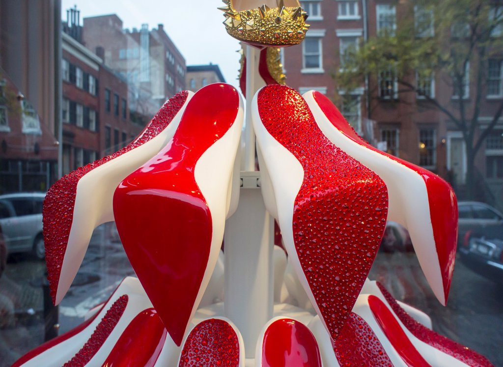 The Christian Louboutin shoe store in the West Village neighborhood of New York displays their Christmas tree window decoration made of their signature red sole shoes : Stock Photo