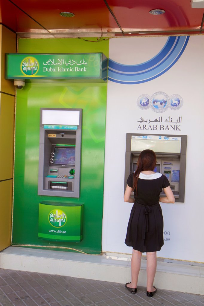 Stock Photo: 1566-1210663 United Arab Emirates, U A E , UAE, Middle East, Dubai, Deira, Al Rigga, Al Maktoum Road, Dubai Islamic Bank, Arab Bank, ATM, self-service, woman, English, Arabic, language,