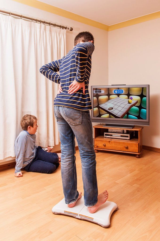 Stock Photo: 1566-1212211 A 13 year old boy playing on a Nintendo Wii Fit board with brother watching