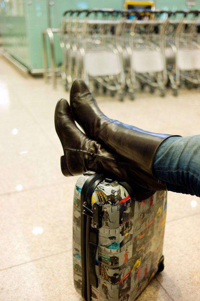 piernas de mujer descansando apoyadas en una maleta en el aeropuerto, woman resting with the legs on a suitcase at the airport : Stock Photo