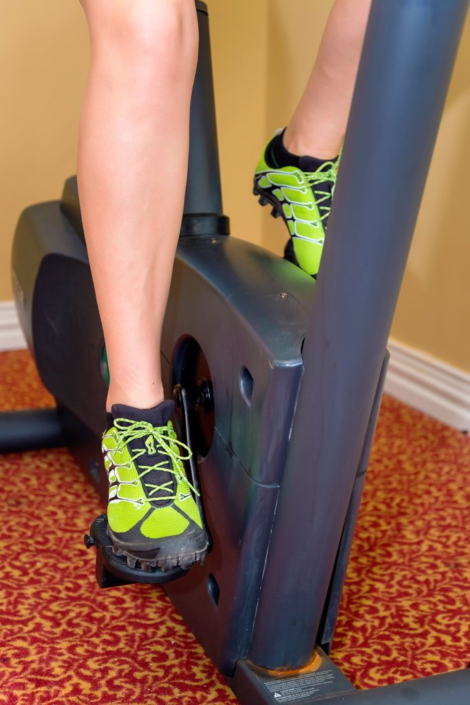 Legs of female, 45, Caucasian, working out on cycling exercise machine, Texas, USA : Stock Photo