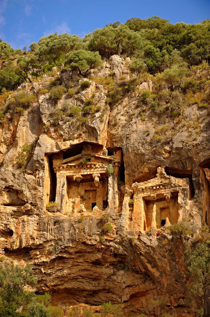 The Hellenistic temple fronted Tombs of Kaunos, 4th - 2nd cent  B C , just outside the archaeological site of Kounos on the oposite side of the Calbys river from Dalyan, Turkey  Kaunos is on the border of Lycia & Caria and the Kaunos rock tombs differ sli : Stock Photo