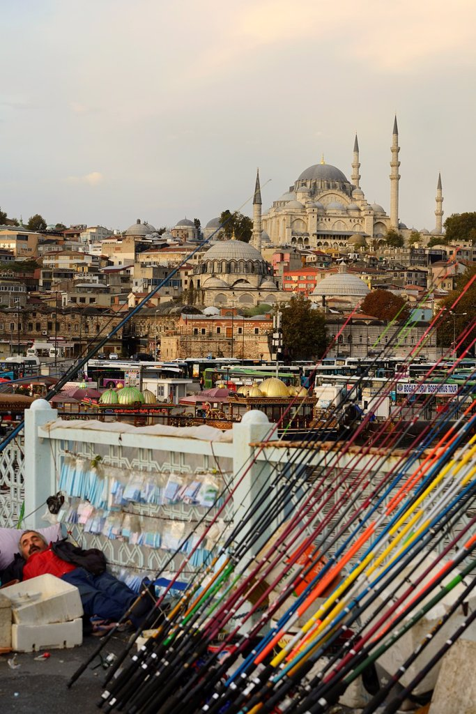 Stock Photo: 1566-1213481 Man sleeping on Galata Bridge with fishing rods over Golden Horn with Suleymaniye Mosque Istanbul
