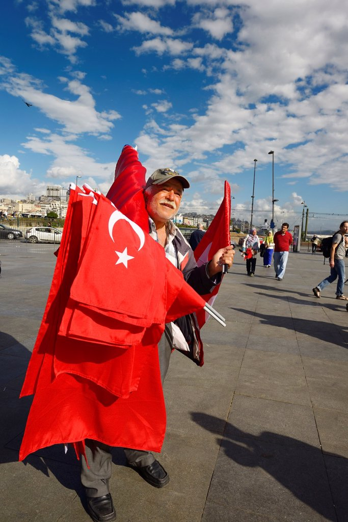 Stock Photo: 1566-1213484 Turkish flag seller in the square between Yeni Camii New Mosque and Egyptian Spice Bazaar Istanbul