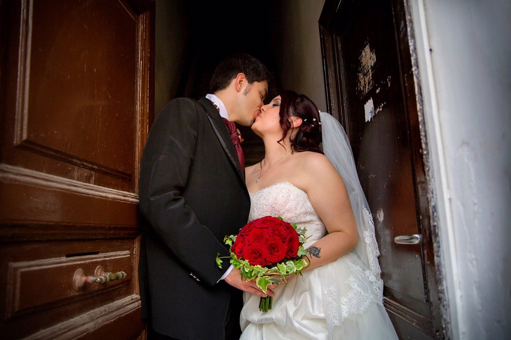 Wedding couple kissing on a doorstep : Stock Photo