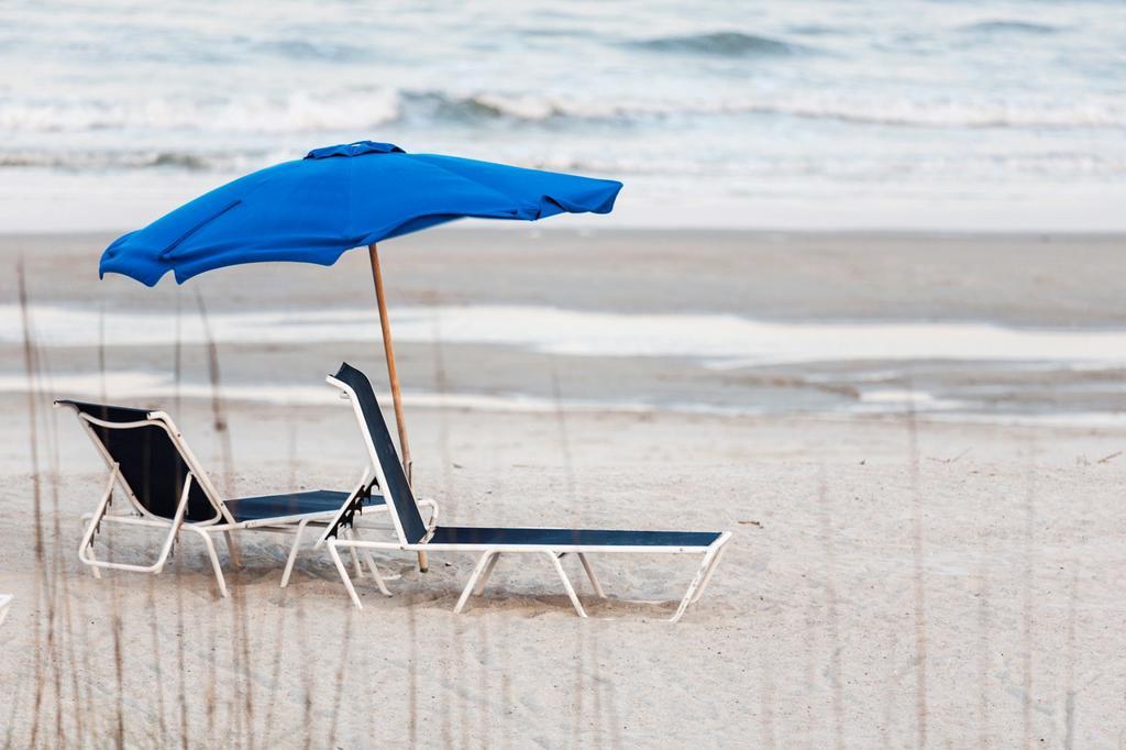Empty beach lounge chairs under beach umbrella at Amelia Island, Florida : Stock Photo
