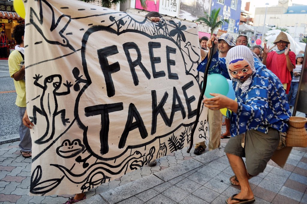 Naha, Okinawa, Japan, people along Kokusai-dori protesting against the American military occupation of Okinawa, the use of V-22 Osprey helicopters and the desctrucion of Yanbaru forest near Takae village : Stock Photo