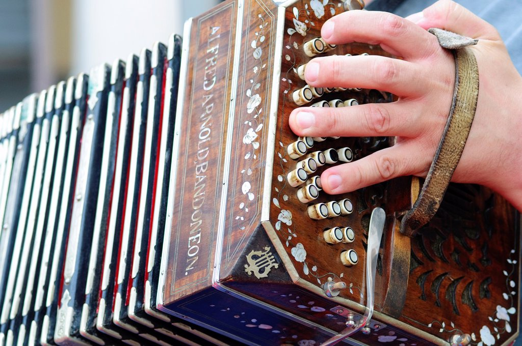 Stock Photo: 1566-1217764 Detail of a Hand Playing the Bandoneon, Traditional Tango Musical Instrument