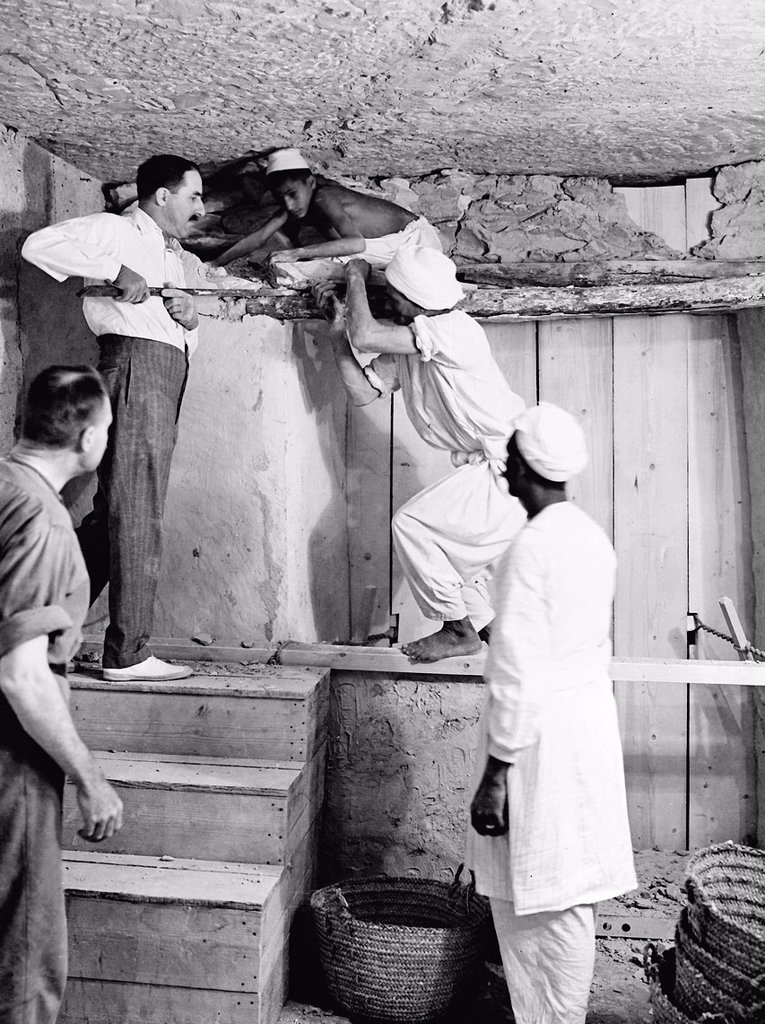 Howard Carter who discovered Tutankhamun´s Tomb in the Valley of the Kings, Luxor, Egypt  November 1922  Carter using a pry bar inside the tomb  From the archives of Press Portrait Service - formerly Press Portrait Bureau   From the archives of Press Portrait Service formerly Press Portrait Bureau : Stock Photo