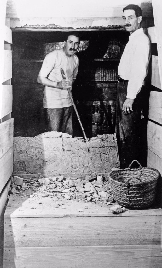Howard Carter who discovered Tutankhamun´s Tomb in the Valley of the Kings, Luxor, Egypt  November 1922  At the opening of King Tutankhamun´s tomb during the entry into the sealed chamber with Howard Carter left inside and A C  Mace right outside of the broken wall  From the archives of Press Portrait Service formerly Press Portrait Bureau : Stock Photo
