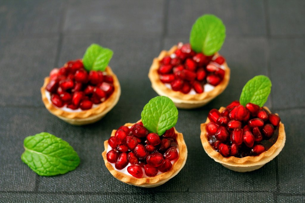Tartlets with cheese and pomegranates : Stock Photo
