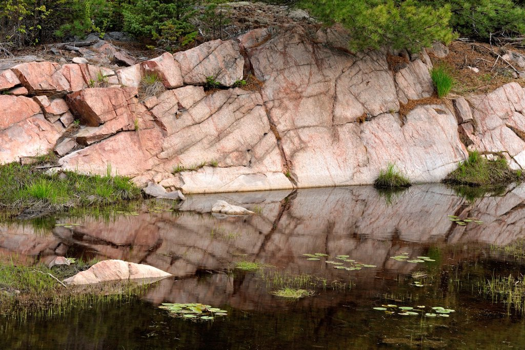 Canadian Shield granite outcrops reflected in a beaver pond, Killarney, Ontario, Canada : Stock Photo